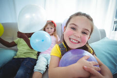 Smiling kids playing with balloons Stock Photo