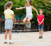 Smiling kids playing with chinese jumping rope Stock Photos