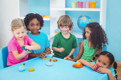 Smiling kids playing with modelling clay Royalty Free Stock Photos