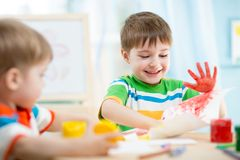 Smiling kids playing and painting Stock Images