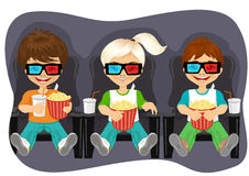 Smiling kids with popcorn watching 3D movie Stock Image