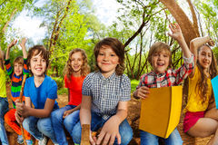 Smiling kids reading a book in the summer forest royalty free stock images