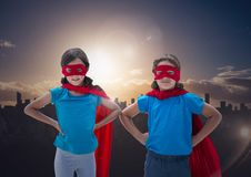Smiling kids in red cape and mask standing with hand on hip against cityscape Stock Photo