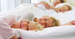 Smiling kids relaxing on bed while parents sleeping in background 4k. Portrait of smiling kids relaxing on bed while parents sleeping in background 4k stock video