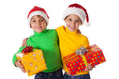 Smiling kids in Santa hats with gift boxes Royalty Free Stock Photo