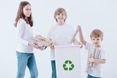 Smiling kids segregating paper waste stock photo