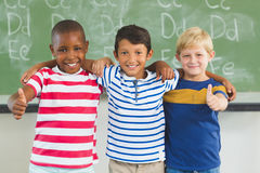 Smiling kids showing thumbs up in classroom Royalty Free Stock Image