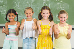 Smiling kids showing thumbs up in classroom Stock Images