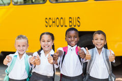 Smiling kids showing thumbs up in front of school bus Royalty Free Stock Image