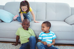 Smiling kids sitting by the couch Stock Image