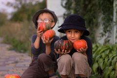 Smiling kids sitting with Halloween pumpkins Royalty Free Stock Image