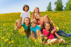 Smiling kids sitting together on the green  grass Stock Images