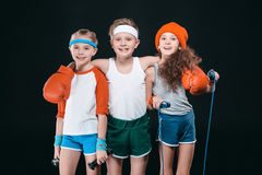 Smiling kids in sportswear posing with sport equipment and looking at camera royalty free stock image