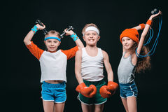 Smiling kids in sportswear posing with sport equipment and looking at camera royalty free stock photos
