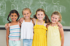 Smiling kids standing with arm around in classroom Royalty Free Stock Photo