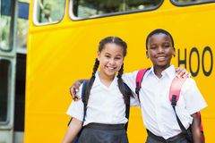 Smiling kids standing in front of school bus Stock Photos