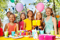 Smiling kids standing next to the birthday cake Stock Images