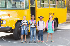 Smiling kids standing together in front of school bus Stock Photography