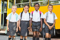 Smiling kids standing together in front of school bus stock photo