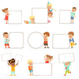 Smiling kids standing with white blank boards set. Happy little boys and girls in casual clothes holding empty posters Royalty Free Stock Images