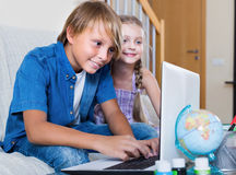 Smiling kids surfing internet on laptop Stock Photography