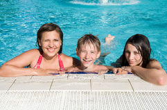 Smiling kids in swimming pool. Kids relaxing in a row on side of swimming pool Stock Images