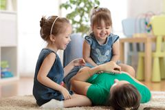 Smiling kids and mom having a fun pastime on floor in children room at home. Smiling kids and their mom having a fun pastime on floor in children room at home Stock Image