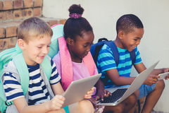 Smiling kids using a laptop and digital tablet on stairs. At school Stock Images
