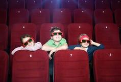Smiling kids watching cartoons. At the cinema stock photos