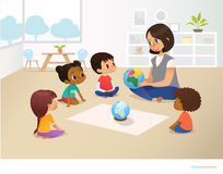Smiling kindergarten teacher shows globe to children sitting in circle during geography lesson. Preschool activities