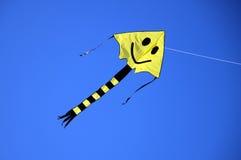 Smiling kite. Yellow smiling kite,  blue, beach Royalty Free Stock Images