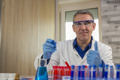 Smiling Lab Technician Giving Thumbs Up in Laboratory. Laboratory researcher filling test tubes with chemical liquid. Pipette dropping red sample into a test Stock Photo