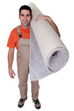Smiling laborer carrying carpet Stock Photo
