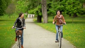 Smiling Ladies on the Bikes are Riding in the Park During the Spring.Two Active Girls Wearing Jackets and Jeans are