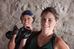 Smiling Ladies Holding Kettlebells. Pair of smiling ladies holding kettlebell weights Royalty Free Stock Photography
