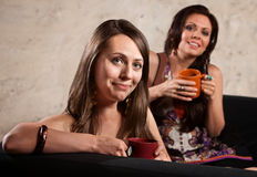Smiling Ladies on Sofa with Mugs Royalty Free Stock Image