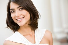 Smiling lady. Portrait of smiling lady with brown hair on the background of columns Stock Images