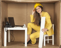 Smiling lady architect sitting in office, holding building plans Stock Images