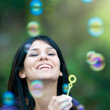 Smiling lady blowing bubbles. Beautiful young latin lady smiling and blowing bubbles outdoor in the nature Royalty Free Stock Images