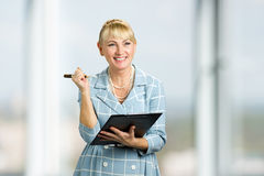 Smiling lady with clipboard and pen. Royalty Free Stock Images