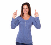 Smiling lady crossing fingers while standing Stock Images