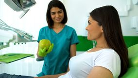 Smiling lady dentist giving green apple to patient, healthcare recommendations. Stock photo stock photo