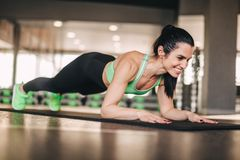 Smiling lady doing plank in gym royalty free stock photography