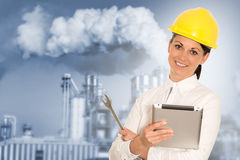 Smiling lady engineer with a tablet and wrench against the facto. Ry. Blurred background Royalty Free Stock Image