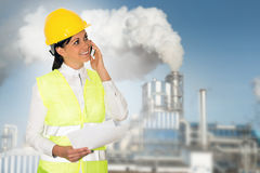 Smiling lady engineer talking on the phone and the factory in th Royalty Free Stock Image