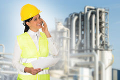 Smiling lady engineer talking on the phone and the factory in th. E background stock images