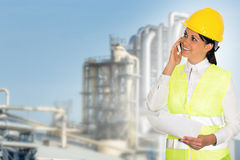 Smiling lady engineer talking on the phone and the factory in th. E background Stock Photography