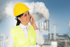 Smiling lady engineer talking on the phone and the factory in th Royalty Free Stock Photo