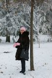 Smiling lady in a fur coat in the winter forest stock photography