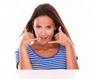 Smiling lady gesturing a phone calling sign. While looking at camera front view in white background Royalty Free Stock Photo